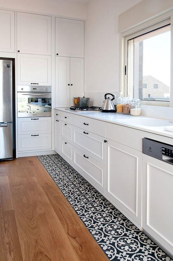 Mintás laminált padló és kő burkolat átmenet a konyhában.