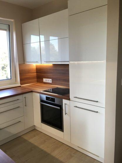 Az elkészült konyha felfele nyíló ajtókkal, hosszúkás fogantyúkkal és a beépített gépekkel egy letisztult eleme lett a lakásnak.