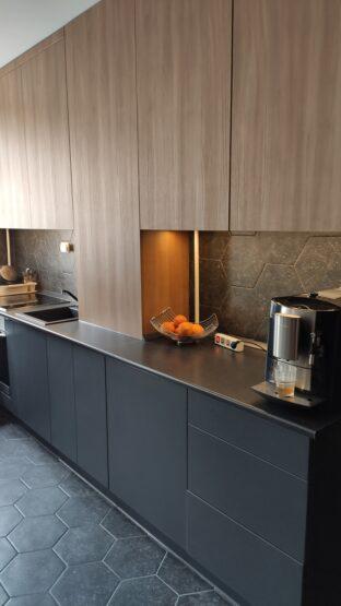 A fogantyú nélkül nyíló ajtók igazán moderné teszik az antracit színű konyha megjelenését.
