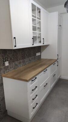 Fehér konyha marás mintás ajtókkal.