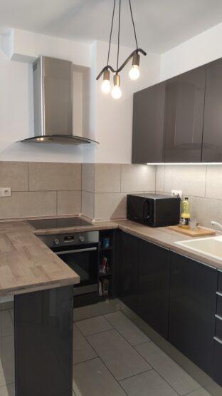 Magasfényű szürke konyha Inox színű lábazati takaróval egészült ki, ami így remek összhangba hozza a konyhát a hűtővel.