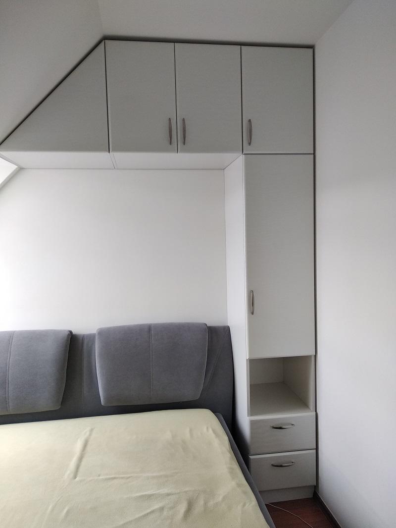 A képen látható tetőtéri hálószoba szekrény több funkciót is betölt.