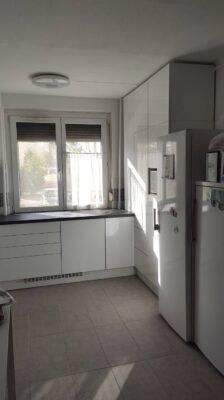 A fehér panelkonyha fényes akril ajtókkal és extra ellenálló felületű Lechner konyhai munkalappal készült.