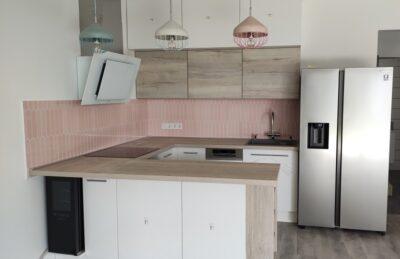 Az U-alakú konyhabútor végét egy nyitott polccal zártuk le. Valamint egy nem beépíthető borhűtő és egy side by side hűtő is helyet kapott.