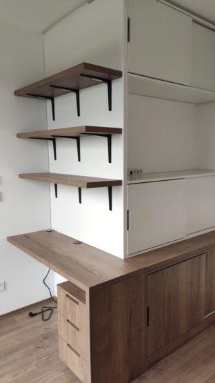 A térbe beugró falat körbeépítő egyedi hálószobabútor komód része a ruhák számára alkalmas, másik része pedig egy dolgozó saroknak ad helyet.