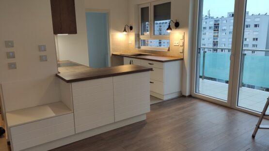 Az egyedi tervezésű konyha különlegessége a nappali felöli oldal. Ugyanis egyedileg megtervezett csíkozott marású ajtók borítják.