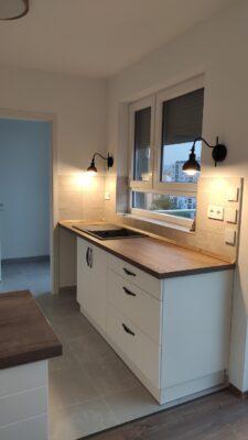 Fehér konyhabútor mosogatóval az ablak alatt