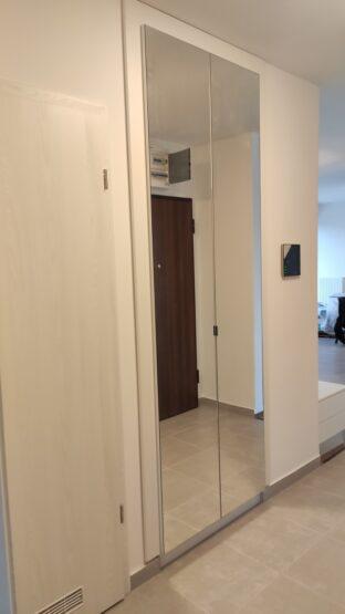 Az egész ajtóban tükrös előszobabútor belsejében akasztó és cipők tárolására alkalmas polc található.
